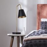 Gold and black bed lamp next to a navy and pink bed.